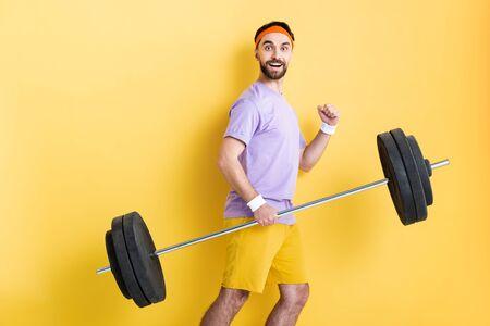 glücklicher Sportler mit schwerer Langhantel beim Gehen auf Gelb Standard-Bild