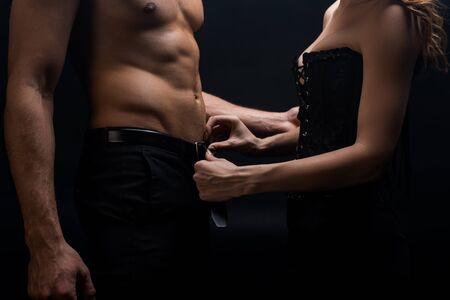 Cropped view of sensual woman taking off belt of shirtless man isolated on black 免版税图像