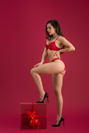 seductive girl in lingerie and high heeled shoes stepping on large gift box isolated on red