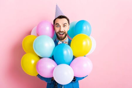 bearded man in party cap smiling near colorful balloons on pink