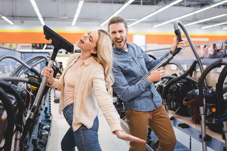 boyfriend playing with vacuum cleaner and girlfriend singing in home appliance store