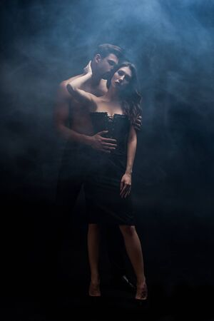 Per tutta la lunghezza dell'uomo muscoloso che bacia la donna su sfondo nero con fumo