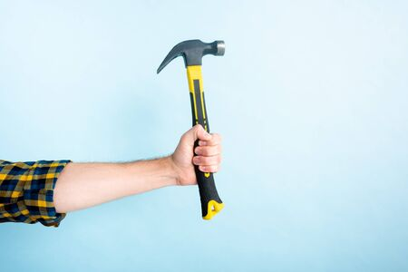 cropped view of workman holding hammer isolated on blue