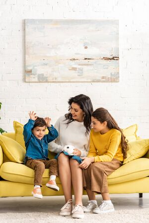 happy children and cheerful mother sitting on sofa with white funny rabbit 스톡 콘텐츠 - 139336887