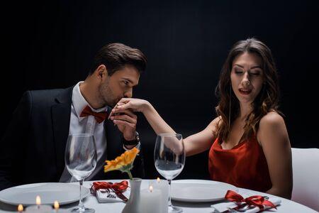 Eleganter Mann, der die Hand einer attraktiven Frau während des romantischen Abendessens küsst, isoliert auf Schwarz