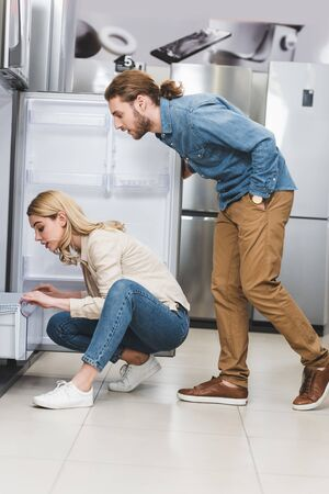 side view of boyfriend and girlfriend looking at fridge in home appliance store