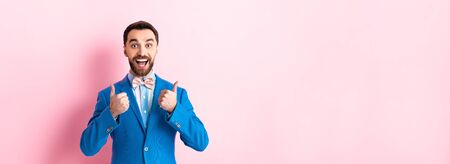 panoramic shot of cheerful bearded businessman showing thumbs up on pink Banque d'images