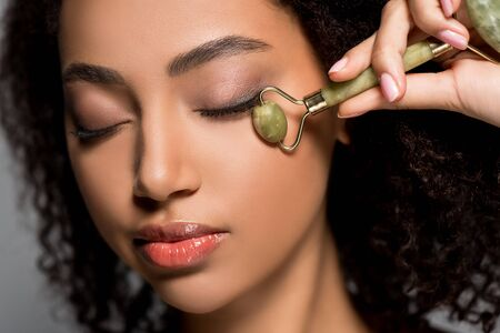 african american woman with closed eyes using jade roller, on grey