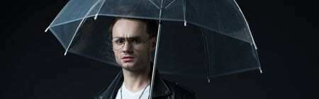 worried stylish brutal man in biker jacket with umbrella isolated on black, panoramic shot