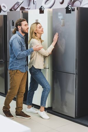 boyfriend pointing with hand and smiling girlfriend touching fridge in home appliance store