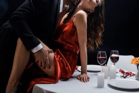 黒の上に孤立したワインと一緒にテーブルの上に美しい女性の腰を保持しているスーツを着た男性のクロップドビュー