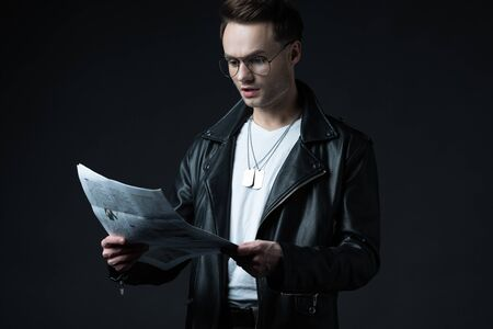 shocked stylish brutal man in biker jacket with newspaper isolated on black Stock Photo
