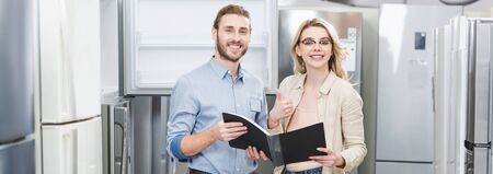 panoramic shot of smiling consultant holding folder and woman showing like in home appliance store