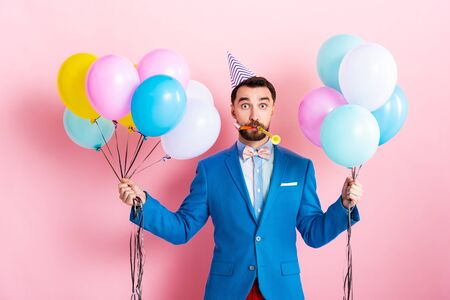businessman in party cap holding balloons on pink Banque d'images