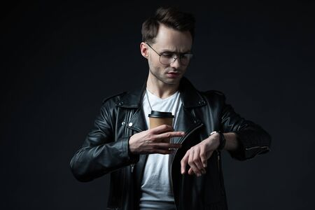 stylish brutal man in biker jacket looking at wristwatch with coffee to go isolated on black
