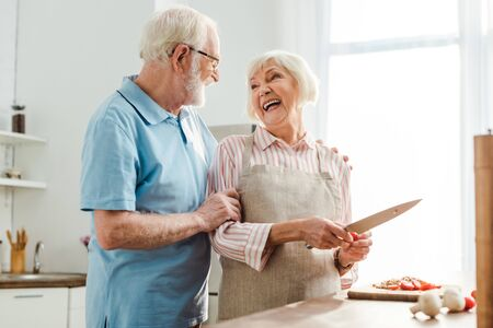 Senior man hugging smiling wife while cutting vegetables on kitchen table