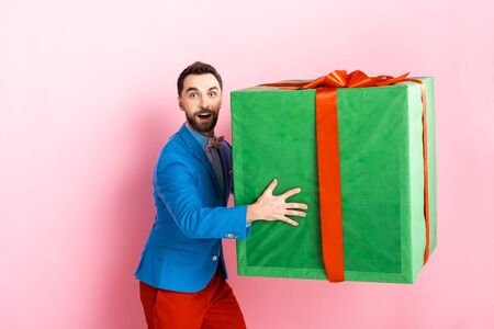 surprised businessman holding huge gift box on pink