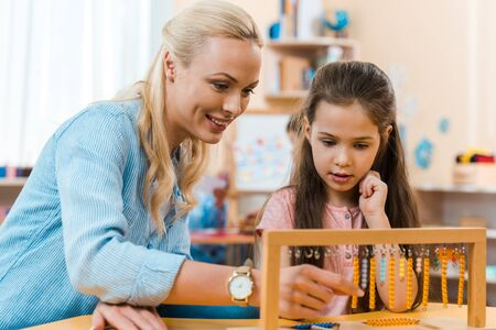 Profesor sonriente y niño jugando al juego de madera en la mesa en la clase montessori