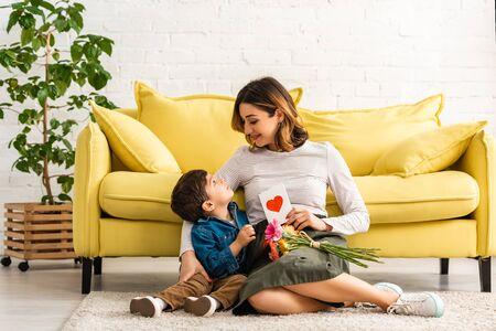 微笑的女人看着可爱的儿子坐在地板上,手上拿着母亲节卡片和鲜花