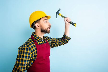 side view of surprised workman holding hummer isolated on blue