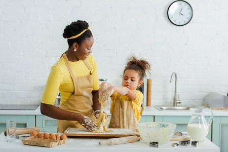 joyeuse mère et fille afro-américaine pétrir la pâte près des ingrédients dans la cuisine