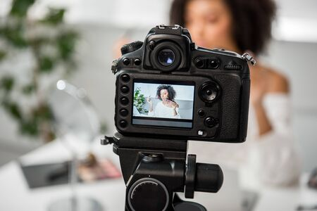selective focus of digital camera with african american girl holding palette with lip gloss and cosmetic brush on display 스톡 콘텐츠