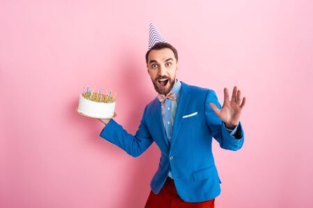excited businessman holding birthday cake and looking at camera on pink