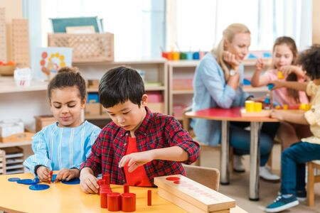 Selective focus of kids playing games with children and teacher at background in montessori school Banque d'images
