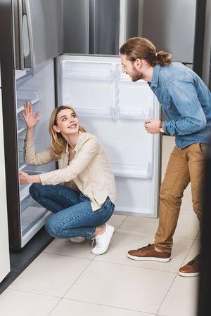 boyfriend talking with smiling girlfriend near fridge in home appliance store