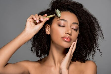 beautiful african american girl with closed eyes using jade roller, isolated on grey
