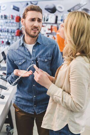 Triste novio hablando con novia con smartphone en tienda de electrodomésticos Foto de archivo