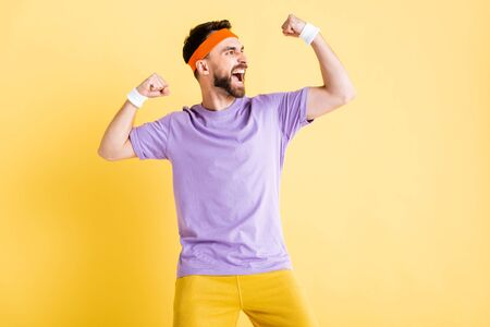 excited bearded man showing muscles isolated on yellow 写真素材