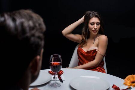 Enfoque selectivo de la mujer sensual tocando el cabello mientras cena con el hombre aislado en negro Foto de archivo