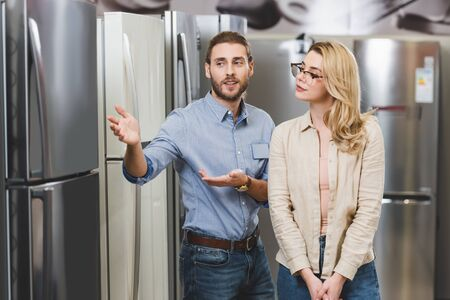 consultant pointing with hands at fridge and talking with woman in home appliance store