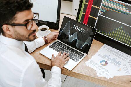 El enfoque selectivo del comerciante bi-racial usando laptop con letras forex