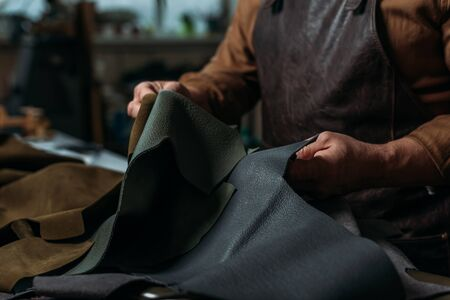 partial view of shoemaker holding piece of genuine leather in workshop