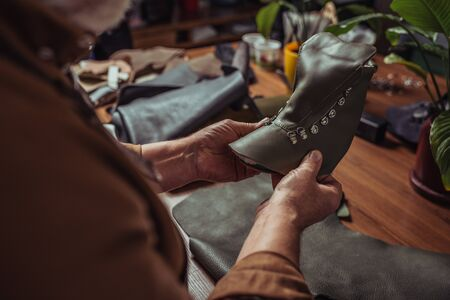 cropped view of shoemaker holding leather detail of unfinished shoe in workshop