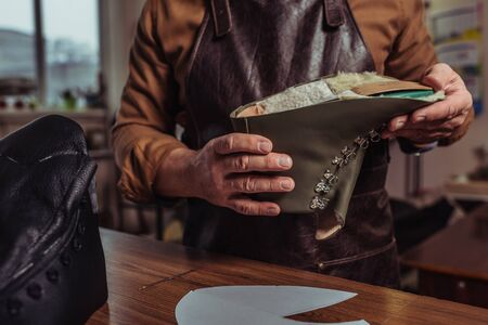 Ausgeschnittene Ansicht eines Schusters, der Lederdetails eines unfertigen Schuhs in der Werkstatt hält Standard-Bild