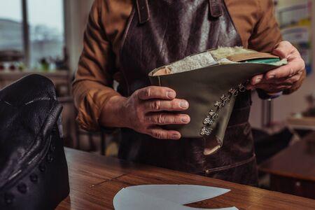 Vista recortada del zapatero sosteniendo el detalle de cuero del zapato sin terminar en el taller Foto de archivo
