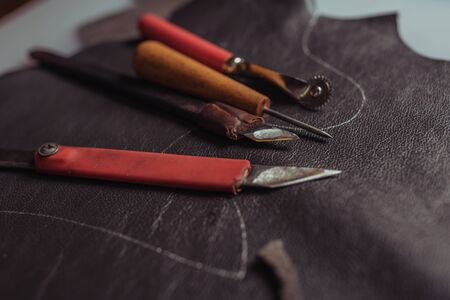 selective focus of cutters, awl and tracing wheel on genuine leather in workshop