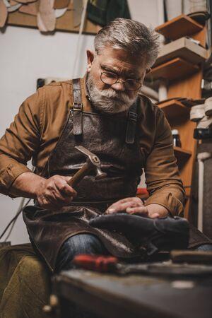senior, bearded shoemaker holding shoe while repairing shoe in workshop