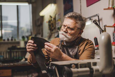 senior, attentive cobbler holding piece of genuine leather near sewing machine Reklamní fotografie