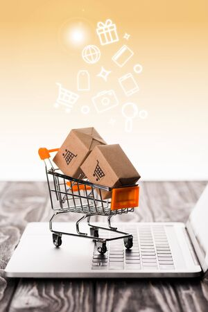 selective focus of toy shopping cart with small carton boxes on laptop keyboard near illustration on orange, e-commerce concept