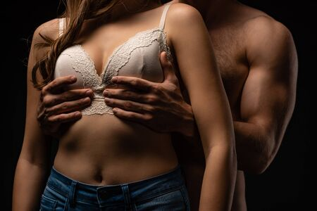 cropped view of passionate young man touching breast of girlfriend isolated on black