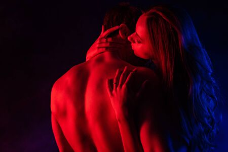 namiętna kobieta całująca rozebranego chłopaka z torsem w czerwonym świetle na czarnym tle