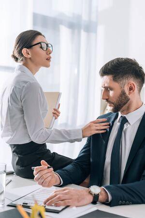 Attraktive Sekretärin, die auf dem Tisch sitzt und den Geschäftsmann im Büro berührt