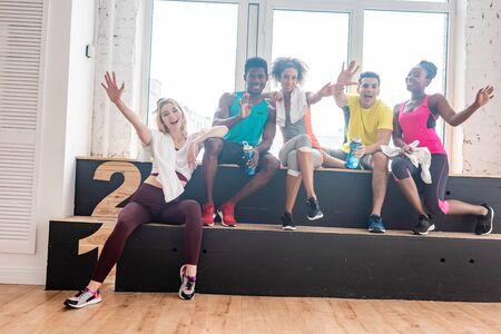 Smiling multiethnic dancers greeting at camera in dance studio Standard-Bild