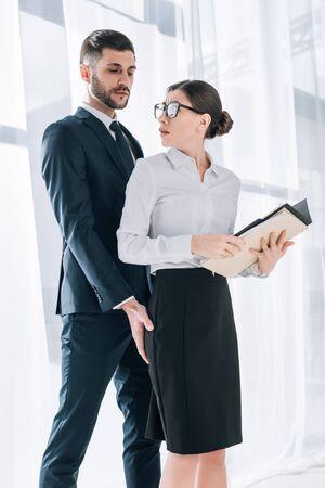 Gut aussehender Geschäftsmann, der den Hintern einer schockierten Sekretärin im Büro berührt