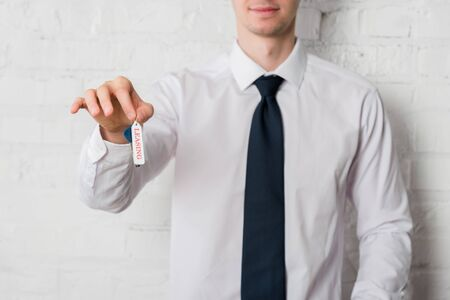 cropped view of happy realtor in suit holding key with leasing lettering on white