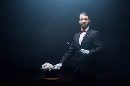 happy magician in suit showing trick with wand and white rabbit in hat, dark room with smoke